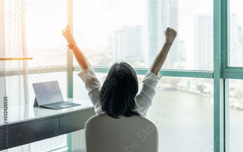 Fototapeta Business achievement concept with happy businesswoman relaxing in office or hotel room, resting and raising fists with ambition looking forward to city building urban scene through glass window obraz