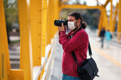 Fototapeta A photographer journalist shoot to reckless people on crowded street with a mask in a quarantine period because of pandemic global danger