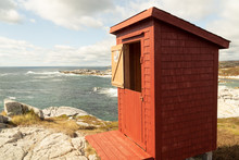 Red Wooden Outhouse,  Closeup, With 2 Part Door, A Slanted Roof And Shingle Siding, Looking Over The Ocean. The Upper Half Of The Door Is Open With A Moon, Bathroom, Sign, Rose Blanche, Newfoundland