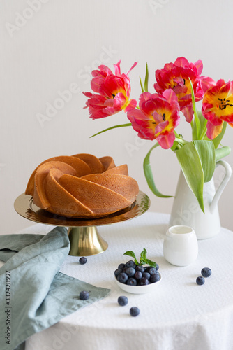 Homemade sponge cake on a white table with tulips and fresh berries Canvas Print