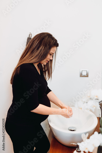 Caucasian pregnant woman smiling and washing hands at home using disinfectant and soap, tap water and cleaning cosmetics - 332430301