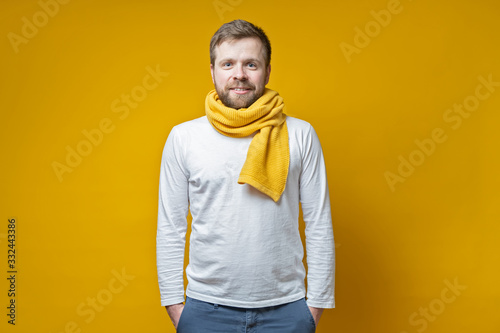 Attractive bearded man in a knitted scarf stands with hands folded in pockets and looks with a cute smile, on a yellow background Canvas Print