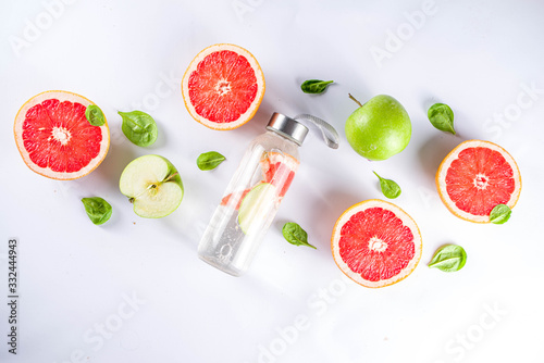 Obraz Balanced nutrition diet, fitness lifestyle concept. Fresh infused drink in glass jar. Detox water, lemonade with grapefruit and green apple.Top view flat lay background - fototapety do salonu