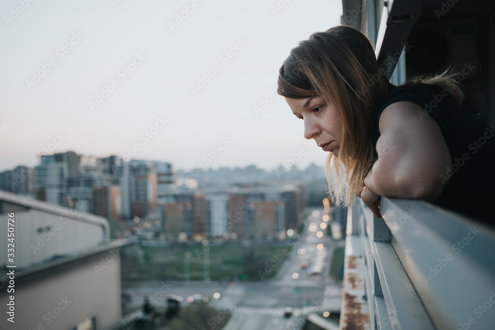 Fototapeta Young sad woman looking outside through balcony of an apartment building