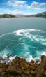 Ocean wave crashing on rock in the bay