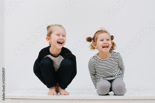 Stampa su Tela Playful brother and sister laugh at home
