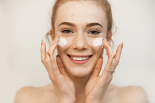 Beautiful Ginger Girl Applying Special Cream On Her Freckled Face While Posing On A Beige Wall