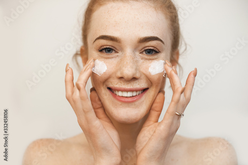Fotografia Beautiful ginger girl applying special cream on her freckled face while posing o
