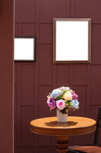 Artificial Rose Flowers In Ceramic Vase On Wooden Round Table With Teak Wood Chair And The Old Blank Picture Frame On Wooden Wall With Blur Door Frame In Foreground, Vintage Style And Vertical Frame