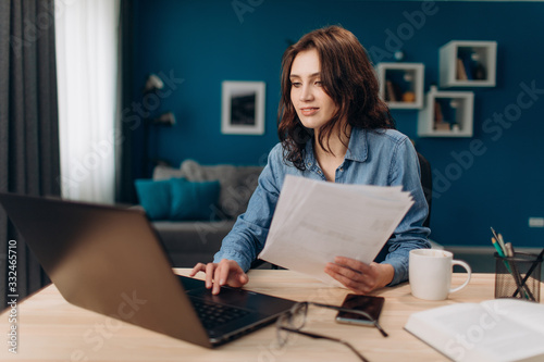 Fotografia Confident young lady with curly hair working on laptop and reading paper documents at home