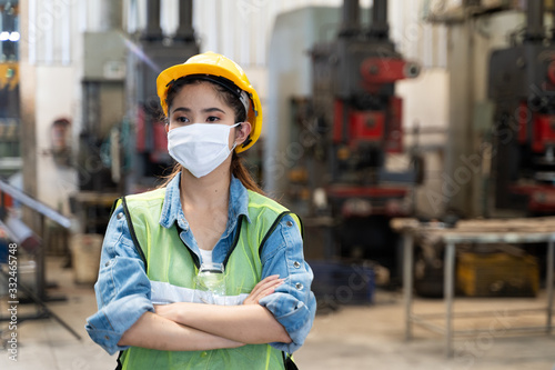 Obraz Asian women worker factory wearing mask protection face for safety stands in machine industrial factory. - fototapety do salonu