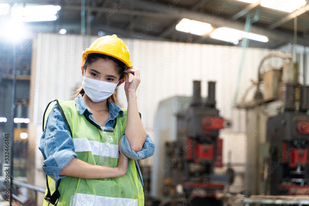 Fototapeta Asian illness women worker factory wearing mask protection face for safety stands in machine industrial factory.