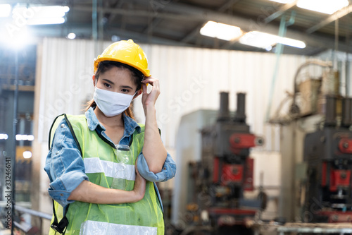Fototapeta Asian illness women worker factory wearing mask protection face for safety stands in machine industrial factory. obraz