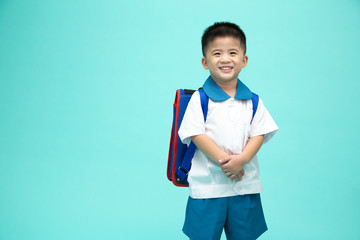 Cheerful smiling asian little boy in a school uniform with backpack having fun isolated on green background, First day of kindergarten and Back to School concept
