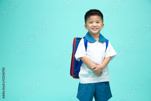Obraz na plátně Cheerful smiling asian little boy in a school uniform with backpack having fun i