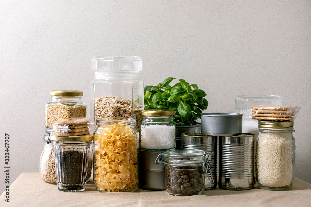 Fototapeta Food supplies crisis food stock for quarantine isolation period. Different glass jars with grains, pasta, cans of canned food, toilet paper, chalkboard handwritten chalk lettering Stay home and relax.
