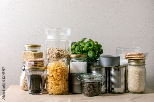 Fototapeta Food supplies crisis food stock for quarantine isolation period. Different glass jars with grains, pasta, cans of canned food, toilet paper, chalkboard handwritten chalk lettering Stay home and relax. obraz