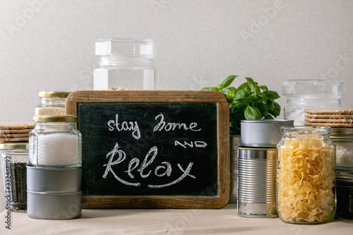 Obraz Food supplies crisis food stock for quarantine isolation period. Different glass jars with grains, pasta, cans of canned food, toilet paper, chalkboard handwritten chalk lettering Stay home and relax. - fototapety do salonu
