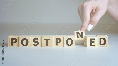 Postponed - hand hold words from wooden blocks with letters, postponed concept, top view background Canvas Print