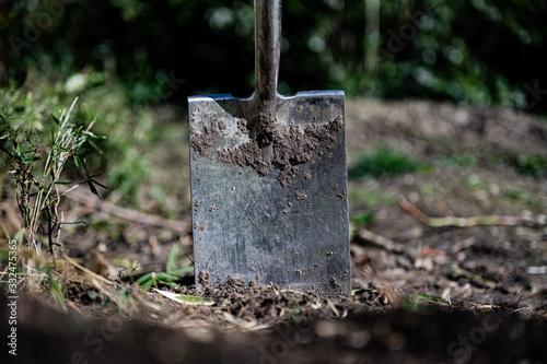 Leinwand Poster Gartenboden wird mit einem Spaten umgegraben