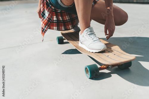 Close-up of female legs in sneakers on a longboard. Fototapeta