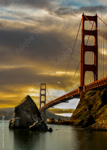 Платно Sunset at the Golden Gate Bridge on a cloudy day the bridge and area is still be