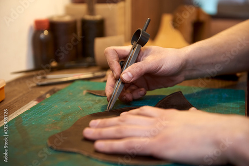Valokuvatapetti Сloseup of the master measuring the width of the seam on natural leather using craft tools