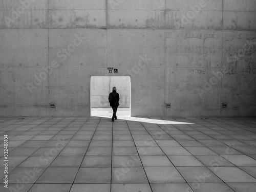 Mujer pasando por una puerta abierta en un muro de hormigón en un lugar solitari Fototapete