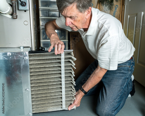 Senior caucasian man changing a folded dirty air filter in the HVAC furnace syst Slika na platnu