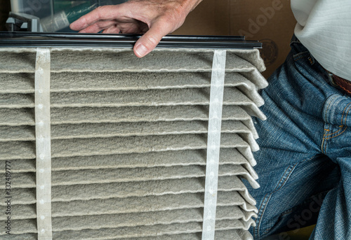 Senior caucasian man looking at the dust in folded dirty air filter in the HVAC Fototapeta