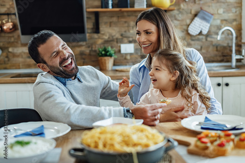 Fototapeta Young happy family having fun while having lunch at home. obraz