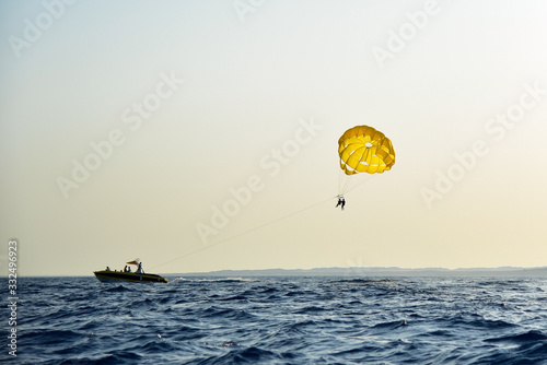 Fototapeta Sea entertainment people parachute over the sea at sunset obraz
