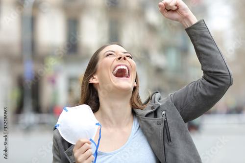 Obraz na płótnie Excited woman celebrating holding mask on city street