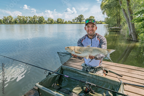 Amur fishing. Fisherman with grass carp fish in hands at lake Canvas Print