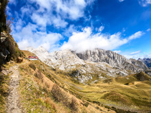 Pathway Leading To An Alpine Cottage In Italian Alps. Sharp Slopes On Both Sides Of The Valley. Hard To Reach Mountain Peaks. There Are Many Mountain Ranges In The Back. Serenity And Peace. Wandering
