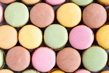 Colorful Tasty Macaroons Stacked In Pile Against Wooden White Surface