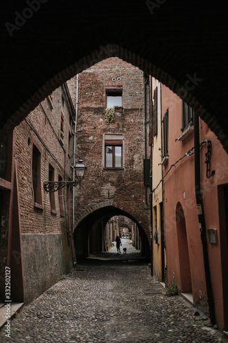 Narrow rocky pavement between old bricked houses under curly arches in shadow  - 332502127