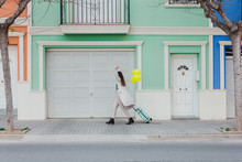 Side View Of Unrecognizable Stylish Female Covering Face With Yellow Balloons Walking With Suitcase On City Street Next To Old Styled Colorful Building