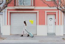 Side View Of Young Stylish Female With Yellow Balloons And Suitcase Walking On City Street Next To Old Styled Colorful Building