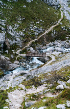 From Above Small Wooden Bridge Above Stormy Mountain River Streaming Through Rocky Mountains In Peaks Of Europe, Asturias, Spain