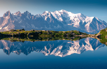 Range of white snowy peaks and hilly seaside reflecting in clear motionless lake in sunny day in Chamonix, Mont-Blanc