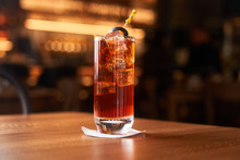Highball Glass With Red Alcohol Cocktail With Ice Cubes Decorated With Stick With Black Olive On Wooden Counter