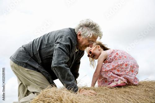 Vászonkép grand-père et petite fille sur meule de foin