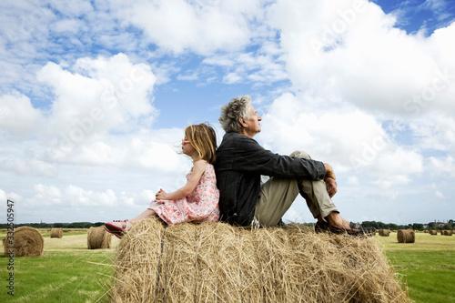Valokuva grand-père et petite fille sur meule de foin