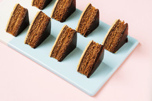 From Above Pieces Of Tasty Chocolate Cake Placed In Rows On Blue Board On Pink Background