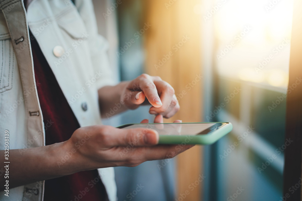 Fototapeta Closeup of female hands using modern smartphone device browsing internet at sunny day during coffee break, businesswoman checking email communicates online on a new project, People Technology Business