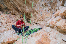Joyful Sportive Female Climber Laughing And Checking Equipment While Resting On Rocks In Summertime