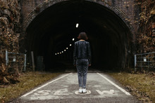 Back View Of Stylish Woman In Black Leather Jacket Looking At Dark Tunnel With Illumination Inside On Marked With Inscription Slow Road In United Kingdom