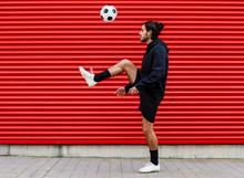 Man Playing Soccer Ball On Str...