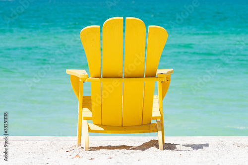 Photo Yellow Adirondack chair with tropical view of emerald water